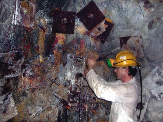تصویر پروفسور تولیس اونستوت استاد زمین شناسی دانشگاه پرینستون در حال بررسی سنگهای یک معدن در آفریقای جنوبی