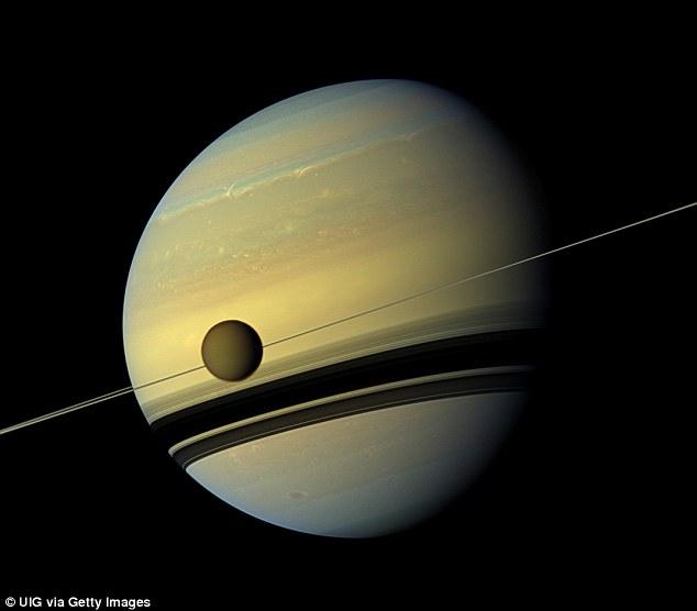 قمر تیتان در نمایی از سیارۀ زحل و حلقه های زیبایش