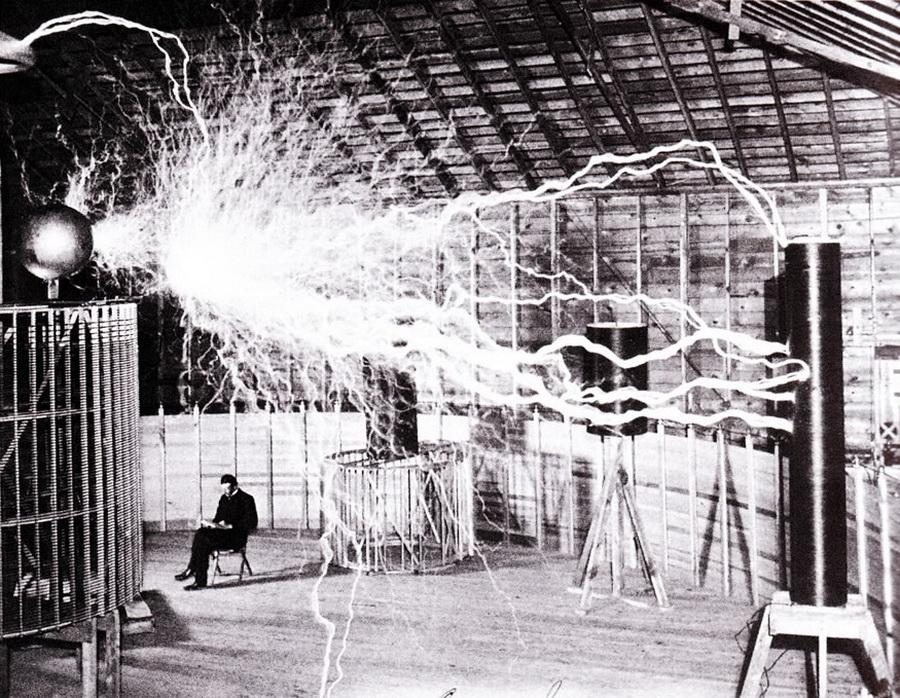 """در این عکس نیکولا تسلا را مشاهده می کنید که در آزمایشگاه کلورادو نشسته  و یک""""فرستنده ذرات اکترومغناطیس"""" میلیون ها ولت انرژی تولید می کند."""