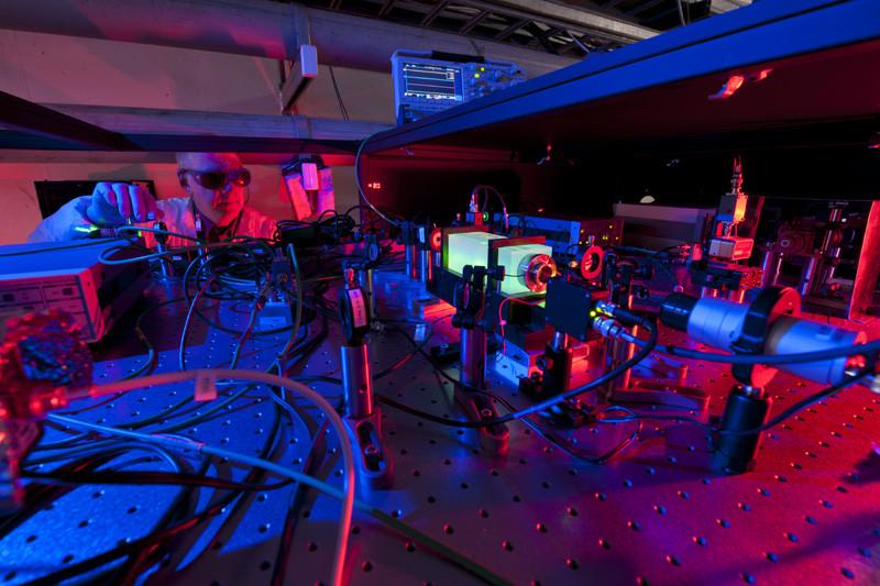 در این عکس یکی از دانشمندان موسسه فرمی را در حال کار با پرتوهای لیزر دستگاه هولومتر می بینید.