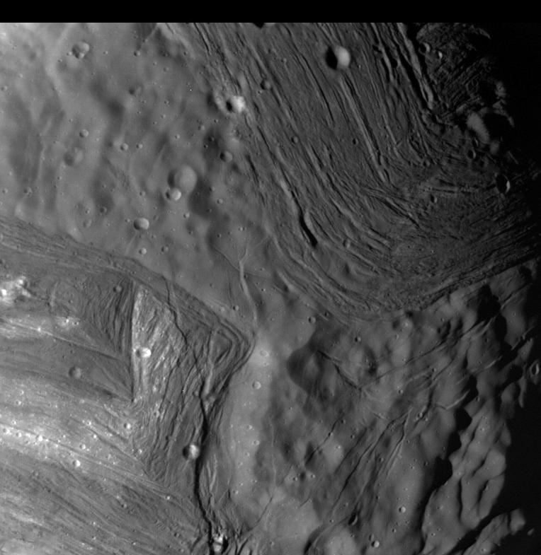 """عکسی از """"میراندا"""" قمر اورانوس که شیارهای موازی و دره های آن به وضوح مشخص است."""