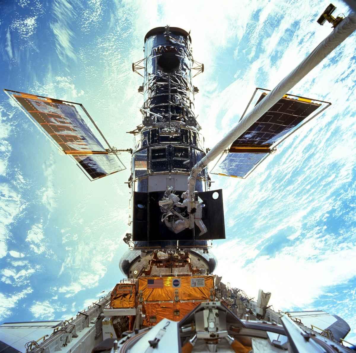 تصویری از دو فضانورد ناسا را می بینید که در سال 1999 بر فراز زمین عملیات تعمیر و ترمیم تلسکوپ هابل را انجام دادند.