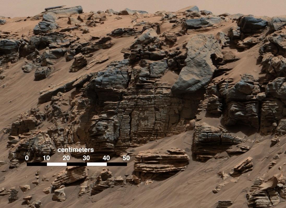 در این تصویر که کنجکاوی به ثبت رسانده، سنگ هایی با لایه های برابر را می بینیم. این الگوهای رسوبی سنگها بر اثر جریان آب دریاچه به وجود آمده اند.