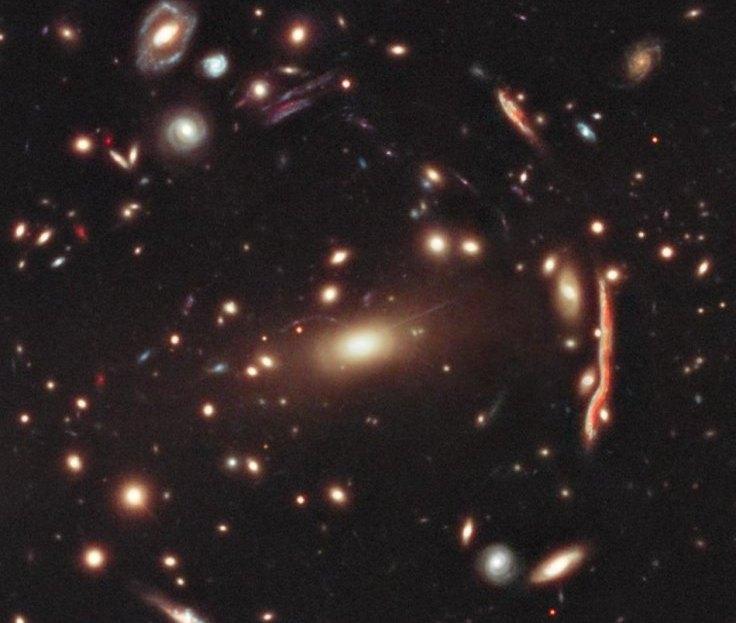 تصویری از خوشه کهکشانی MACS J1206.2-0847 احاطه در ماده تاریک که بدلیل عدسی گرانشی ایجاد شده نور در مسیرشان خم می شود.