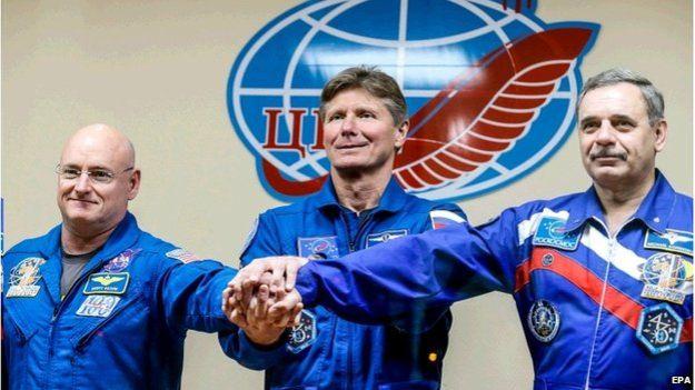 """تصویری از فضانوردان """"کلی"""" ( چپ) """"کورنینکو"""" (راست) که قرار است یکسال در ایستگاه فضایی ساکن شوند و فضانورد """"پادالکا"""" که شش ماه بعد به زمین باز می گردد."""