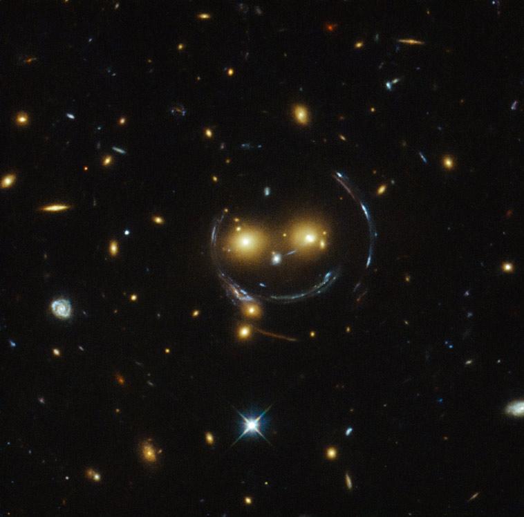 لبخند کیهانی: عکسی که تلسکوپ هابل گرفته بدلیل ایجاد عدسی گرانشی، شبیه یک لبخند کیهانی شده.