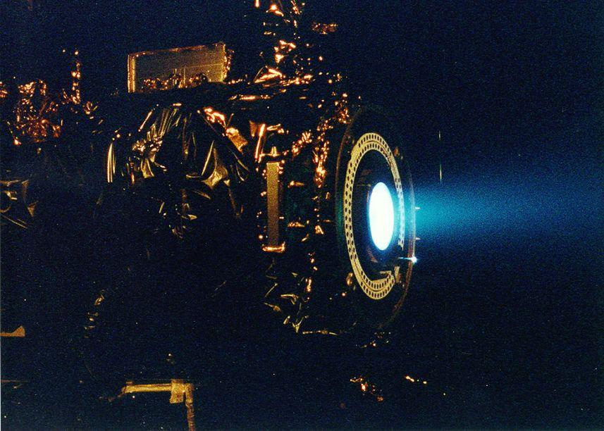آزمایش یک موتور یونی. نور ضعیف آبی که در تصویر مشاهده می شود، گازهای خروجی از اگزوز موتور است که نیروی پیشران آن را تأمین می نماید.