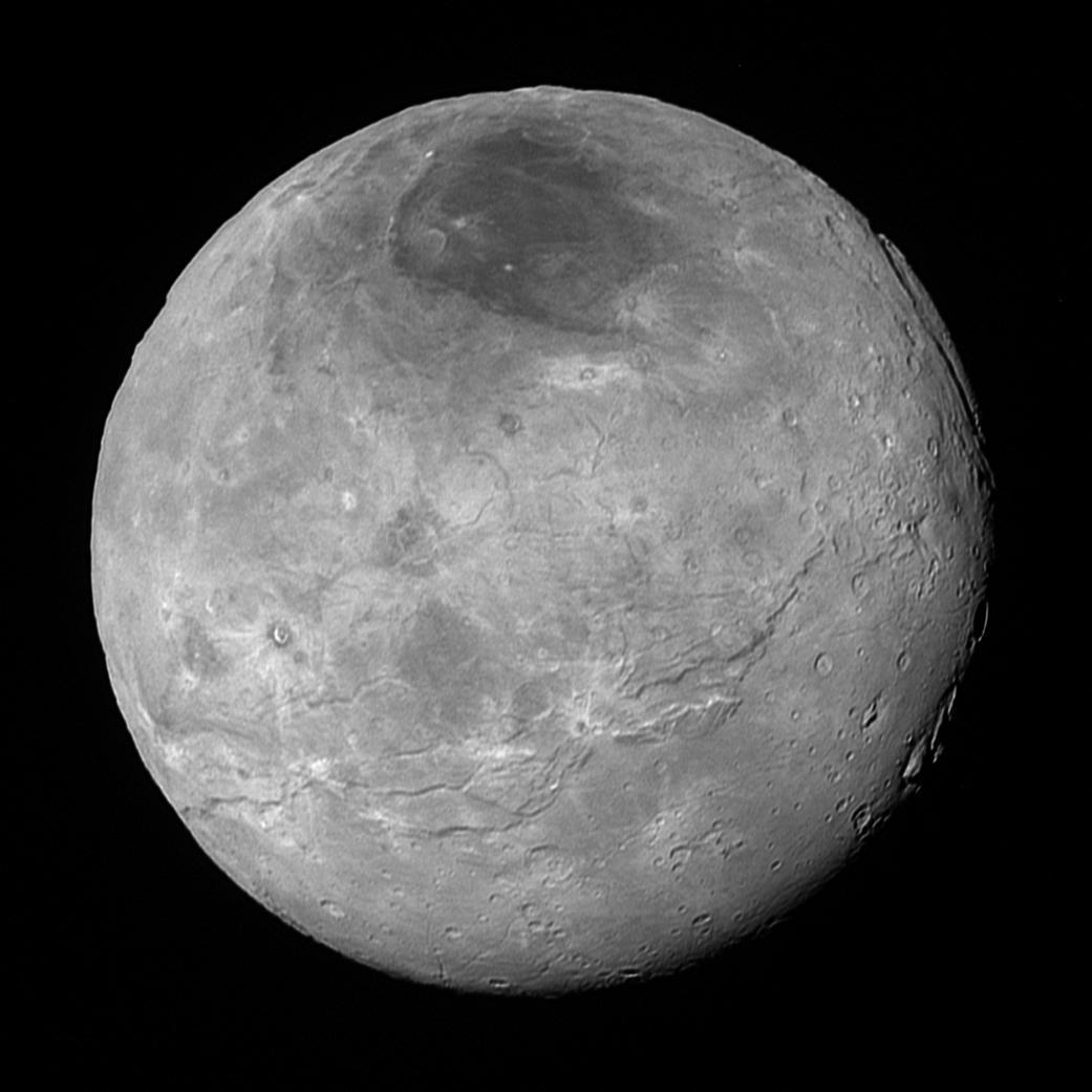 عکس شارون، بزرگ ترین قمر پلوتو که فضاپیمای افق های ۱۰ ساعت پیش از رسیدن به نزدیک ترین فاصله ی پلوتو در ۱۴ جولای ۲۰۱۵، از فاصله ی ۴۷۰ هزار کیلومتری از آن گرفته بود ولی تازه از فضاپیما دریافت شده و وضوحش بسیار بهتر از عکسی از شارون است که در ۱۵ جولای منتشر شده بود. شارون که ۱۲۰۰ کیلومتر قطر دارد، تاریخ زمین شناختی با پیچیدگی های شگفت انگیزی را می نمایاند، از جمله ترَک های زمین-ساختی؛ دشت های شکسته و به نسبت هموار در پایین سمت راست؛ چندین کوه رازگونه با سطح های فرو رفته در سمت راست؛ و ناحیه هایی پر از دهانه ی برخوردی در مرکز و بالا سمت چپ. همچنین الگوهای پیچیده ای از بازتابندگی روی سطح شارون دیده می شود، از جمله رگه های دهانه ای تیره و روشن، و ناحیه ی قطبی شمال آن که با تیرگی آشکاری در بالای تصویر به چشم می آید. اندازه ی کوچک ترین ساختارهای دیدارپذیر در این عکس ۴.۶ کیلومتر است.