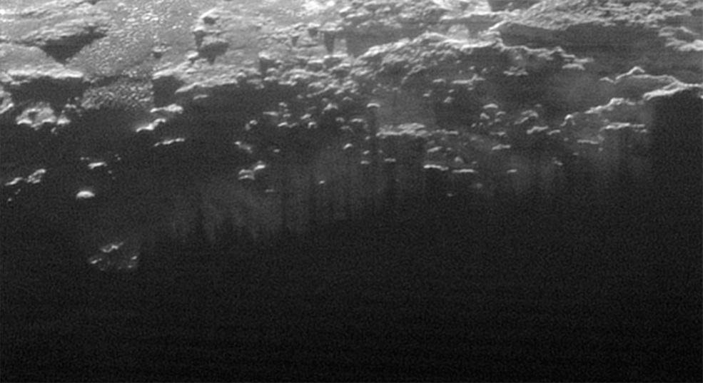 مه نزدیک سطح پلوتو: این عکس بریده ی کوچکی از تصویر گسترده ی هلال پلوتو است که افق های نو درست ۱۵ دقیقه پس از عبور نزدیک از پلوتو ثبت کرده است.خورشیدِ رو به غروب، مه نزدیک سطح پلوتو (ریزگرد) را روشن کرده، در حالی که سایه های همراستای چندین تپه و کوه کوچک، این روشنی را راه راه کرده اند.