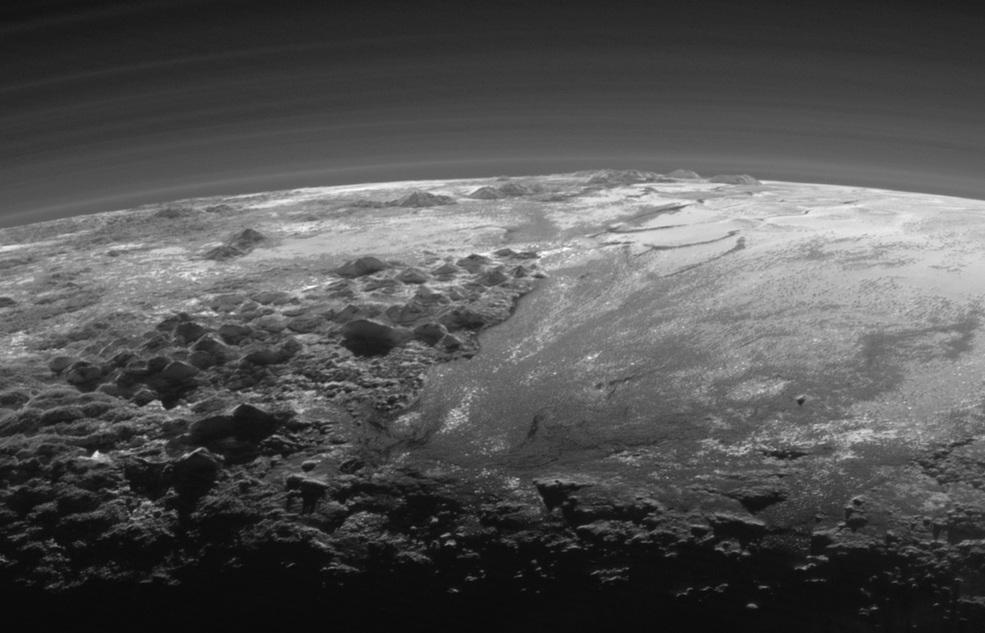 کوه های باشکوه و دشت های یخ زده: در این نما چشم اندازی نزدیک به غروب را از کوهستان های ناهموار و یخی و دشت های یخ زده ی هموار پلوتو نشان می دهد که تا افق کشیده شده اند.در این تصویر پهنه ی هموار فلاته ی اسپوتنیک (سمت راست) در غرب کوه های ناهمواری که بلندیشان به ۳۵۰۰ متر می رسد (سمت چپ) به چشم می خورد، از جمله کوهستان نورگای در پیش زمینه و کوهستان هیلاری در لبه ی افق.
