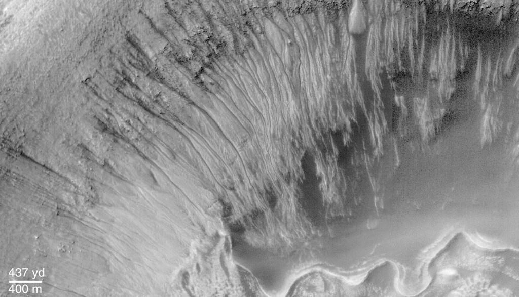 تصویری از رگه های باریک تیره بر روی دیواره های دهانه ای در مریخ، درازای این رگه های تیره که بر اثر آب شور ایجاد شده به چند صد متر می رسد.