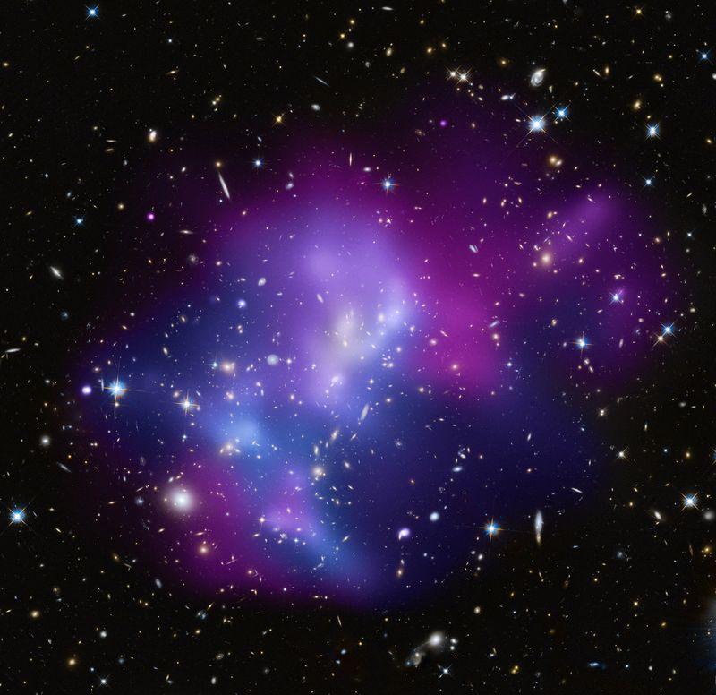 این عکس، خوشه ی کهکشانی عظیم و پر جرم MACS J0717.5 + 3745 را نشان میدهد که ترکیب ِ پیچیدهای از حداقل ۴ خوشه ی کهکشانی مجزا میباشد.
