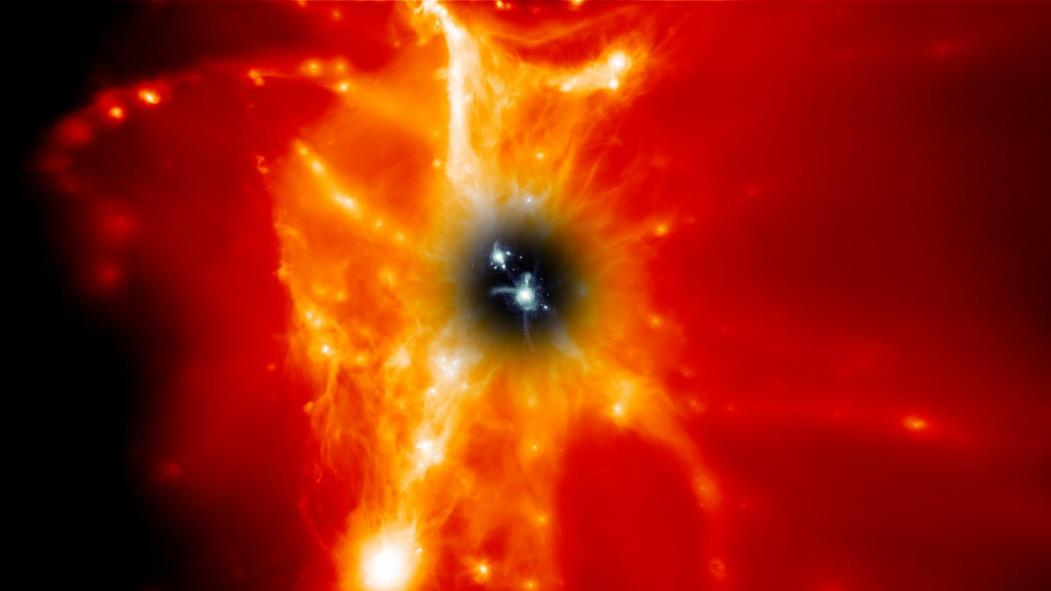 """کهکشان های مارپیچی همچون کهکشان راه شیری، که توسط """"محیط کهکشانی"""" محاصره شده اند و به رنگ سیاه در مرکز تصویر دیده می شوند. به هر حال، """"محیط کهکشانی"""" حاوی گاز های بسیار داغی است که با رنگ های قرمز، نارنجی و سفید مشخص شده اند و از کهکشان های مرکزی سنگین ترند. طیف نگار ریشه ای کیهانی روی تلسکوب هابل یک طیف نگار فرابنفش است که می تواند این رشته ها و توده های گازی را بررسی کند."""
