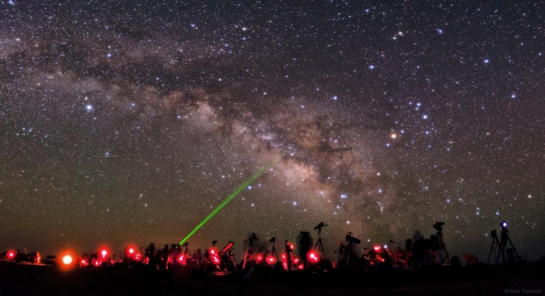 """در این تصویر که پس زمینه ی آن را کهکشان راه شیری پوشانده، یک گروه حدودا ۱۵۰ نفری از مشتاقان نجوم، در ناحیه ی بیابانی """"سه قلعه"""" در شرق ایران به آسمان نظاره می کنند. عکس از: بابک امین تفرشی"""