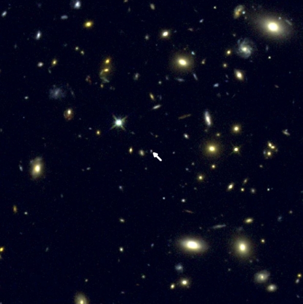 نمایی از کهکشان COSMOS-1908 در مرکز تصویر که با فلش مشخص شده. این عکس توسط تلسکوپ فضایی هابل ناسا ثبت شده است.