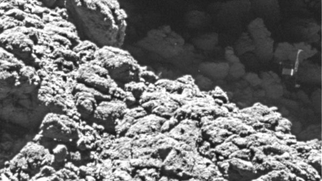 عکسی از کاوشگر فیله نگون بخت در سایه ی یک صخره گیر افتاده است.