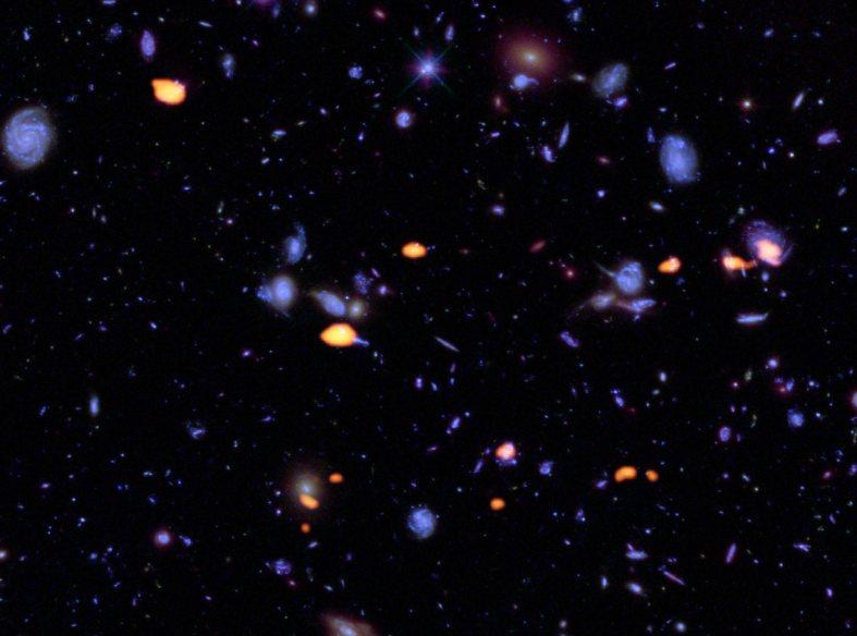 گنجینه ای از کهکشان ها، غنی از مونواکسید کربن (که نشان دهنده پتانسیل شکل گیری ستارگان است) این عکس توسط آرایه آلما(رنگ نارنجی) در میدان فرا ژرف هابل تصویربرداری شده است. عوارض آبی رنگ، کهکشان هایی است که توسط هابل تصویربرداری شده اند.