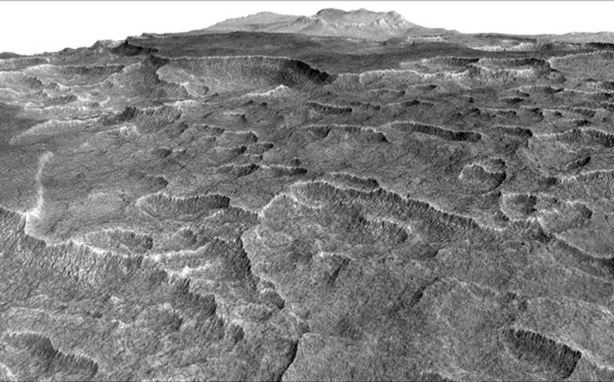 این تصویر فرورفتگی های حلزونی شکلی را در بخش هایی از سیارۀ مریخ نشان می دهد؛ در اینجا این ساختارها محققان را ترغیب کرد تا یخ های مدفون شده را با استفاده از رادارِ نفوذی مدارگرد اکتشافی مریخ ناسا بررسی کنند.