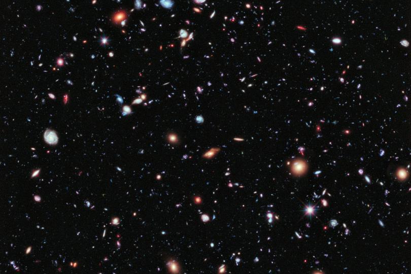 تصویری از زمینهی فراژرف هابل – به جز چند ستاره، باقی لکههای نور هرکدام یک کهکشاناند – برخی با سن 13.2 میلیارد سال